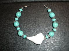Handcrafted bracelet made  with hand picked shell adorned with  blue turquoise beads  w/ toggle clasp . $18.00. Made by Elkira Shells.  Can be purchased by emailing Elkira.Shells@gmail.com