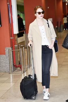 The perfect travel outfit: a cozy henley, skinnies, sneakers, and an easy short-sleeve trench. On Emma Stone: Cos Oversized Poplin Jacket ($175); J Brand Henley T-Shirt ($93); adidas Superstar Sneakers ($80).