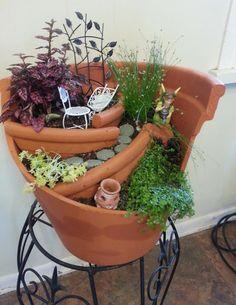 adorable fairy garden in a broken pot