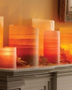 get cheapo clear glass vases, fill with sand, wrap with tissue paper (vary the layers for varying translucence and color), place votives, light, ta-da!!