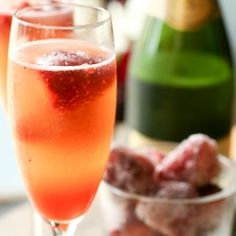 A celebratory glass of guava mimosa paired with frozen strawberries