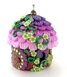 This handmade Fairy Home is crafted around a tiny glass jar, and the roof is molded around the lid of the jar. This enables the roof to be unscrewed to reveal a functional keep-safe vessel. It is the perfect size to hold childrens' teeth, and a fun alternative to leaving teeth under a