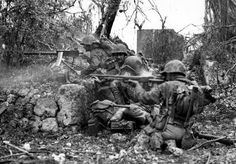 US Marines firing a machine gun Browning M1919 during the fighting on the island of Peleliu. In the foreground is a soldier with an automatic rifle BAR (Browning M1918).