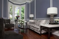 Creating Modern Victorian Interiors - Victorian times were full of detailed decor. Lots of color. The deep, yet dusty blue-grey walls covered in white trim are a great example of Victorian color. Yet, the black and white furniture is very modern.