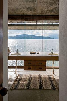 Transposta a parede cega que divide o bloco dos dormitórios e banheiros do restante da casa, a edificação se abre para a vista do mar