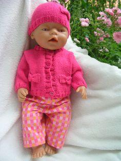 Růžový komplet pro panenku Komplet se skládá z pleteného svetříku a čepičky a bavlněných kalhot. Svetřík se zapíná na 4 knoflíky vepředu, je ozdobený mašličkami stejně jako čepička. Kalhoty jsou v pase do gumy. Vhodné pro panenku Baby Born nebo podobná miminka (cca 42 cm).