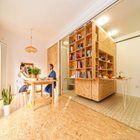 Library-style shelving units slide back and forth to transform a tiny Madrid apartment