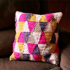Add some cheery colors to a room with this geometric crochet pillow.