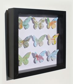 Cut out butterflies from specialized paper. Bend/crease them so they have 3D look. Frame in shadow box.