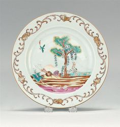 """CHINESE EXPORT PORCELAIN 'VALENTINE' pattern plate: mid- 18th Century  Gilt shell and foliate border . Enamel decoration at center of a tree swagged with floral garlands. Two dogs rest beneath tree and a bird flies above. Diameter 9"""". This pattern occurs in both polychrome and grisaille versions."""
