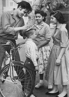 Elvis Presley-on a bicycle-signing an autograph using a young boys head for support. 1950s