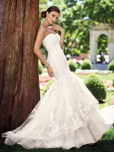This mermaid gown with a scalloped sweetheart neckline and lace appliqué bodice has an asymmetrically dropped waist and back with a layered two-tiered skirt