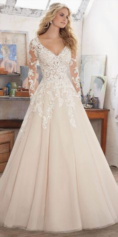 Long Sleeve Wedding Dress Featuring Delicate Crystal Beading on Bodice and Embroidered Appliqués on Tulle. V-Neckline and Open Keyhole Back.