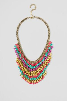 Cheyenne Bib Necklace. The cascading chain bib necklace features alternating rows of pink, teal, purple & gold bugle beads. Perfect colorful necklace for your summer festival outfit.