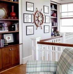 Nautical wall with ship wheel and framed charts.