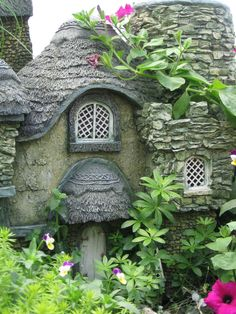 A Pixie Cottage among the Violas and climbing blooms - looks like it's from a storybook