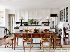 """The kitchen is the hub of the house, with room for a desk and a big breakfast table. """"I thought the more formal lyre-back chairs combined with the French farmhouse table was an interesting juxtaposition,"""" designer Connie Newberry says. Kitchen Tops, Kitchen Dining, Open Kitchen, Dining Area, Dining Table, Table Lamps, Wood Table, Kitchen Cabinets, Wood Chairs"""