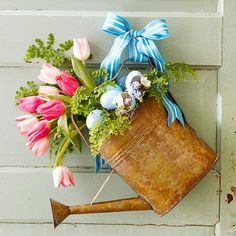 Easter Egg Door Decor.          Welcome spring with a festive Easter door display. Use an old watering can as a flower vase complete with pretty pastel eggshells. Hang the display on the front door to ensure family and friends feel right at home.