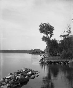Three boys on the shore of Pewaukee Lake. A boat dock and boat house are visible in the background. Pewaukee Lake, Waukesha Wisconsin, Three Boys, Boat Dock, Boathouse, Local History, Historical Society, Old Photos