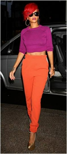 The fearless fashionista goes bold with color, pairing her fire engine red hair with a purple cropped top and orange high-waisted pants, while visiting a London radio station.