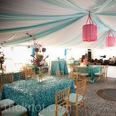 Laguna-blue linens with shimmery teal confetti overlays topped the  tables, and gauzy fabric and ribbon hung from the ceiling for a glam effect.