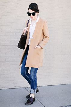 This combination of a tan coat and blue skinny jeans is perfect for off-duty occasions. Finish off your look with black leather oxford shoes.   Shop this look on Lookastic: https://lookastic.com/women/looks/coat-dress-shirt-skinny-jeans/16814   — White Dress Shirt  — Camel Coat  — Black Leather Tote Bag  — Blue Skinny Jeans  — Black Leather Oxford Shoes  — Black Sunglasses