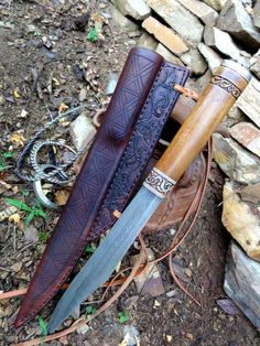 """Anglo-Saxon style broken back seax by Petr Floriánek. """"The blade is welded from wrouht back, twisted nine layer bar, and the steel edge with traces of wrought iron sides  The bolster is of stag antler carved with the designs of Trewhiddle style. The motiv in the same style is carved on the end of the boxwood handle, which is terminatin in a silver cap. The shath is heavy leather, handsewn with linen thread and ornamneted with period motives incised and tooled to leather surface"""""""