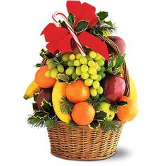 Apples, bananas, grapefruits, pears and tangerines, along with holly and fir, arranged in a wicker basket with handle, topped with a ribbon.