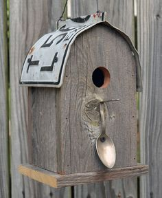 Rustic bird house with a rounded license plate roof and a perch made from a bent spoon.