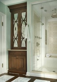 Elegance in the bathroom | Custom Linen closet with mirrored doors and beautifully tiled shower