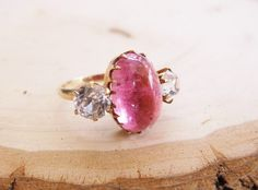 Wonderfully unique 6.28 carat cabochon cut pink tourmaline ring with a 1.15 carat white sapphire on each side.