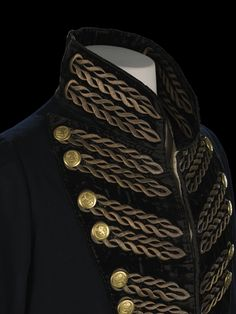 Commander, Honouable East India Company uull dress coat, crcaa 1818.  Tail coat of fine blue wool lined with white silk twill. Large, heavy button back lapel faced with black velvet and embroidered with a twist pattern, outlining the buttonhole. The embroidery is done in satin stitch with metal thread. Each lapel has 10 gilt metal buttons with the coat of arms of the Company. The coat also has a large stand up collar of black velvet embroidered with metal thread.