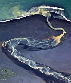 Aerial photograph of a river flowing through a bed of volcanic ash in Iceland.