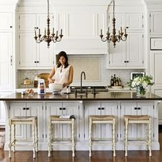 i love this kitchen, the island, the white cabinetry but some country french with the awesome chandeliers over the island and the stools. the like the doors under the island seating overhang, i like the brick style tile backsplash