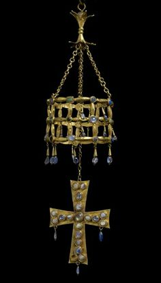 """""""Votive Crown with Hanging Cross"""" A lavishly decorated latticework crown and hanging cross. Part of the Guarrazar Treasure. Crafted out of gold and encrusted with glass, pearls, sapphires, moonstone, and crystals. Made in the 600s near Toledo by the Visigothic royal court as a gift to the Roman Catholic Church. A superb and rare example of Visigothic art. Currently at the National Archeological Museum of Spain."""