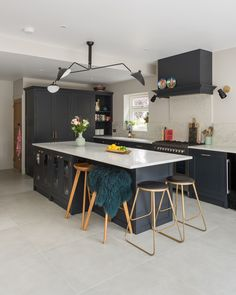 This large kitchen island features glazed cabinets for glassware and bar stool seating.