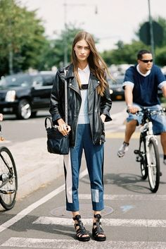 A collared white top is worn with patched denim pants, a moto leather jacket, black sandals and a black crossbody bag.