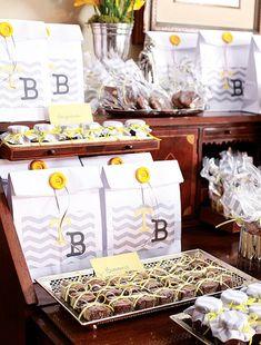 Chá de bebê: Brigadeiros, brownies e cookies foram acomodados numa antiga escrivaninha. Na hora de ir embora, era só rechear o saquinho com as iniciais dos homenageados