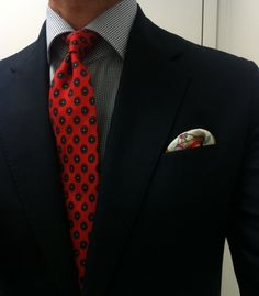 Navy jacket, navy gingham shirt, red tie with navy medallions