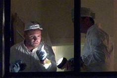 An FBI crime scene investigator points to a fingerprint as a response team gathers evidence at a Delray Beach, Fla., condominium where terrorist suspects in the World Trade Center and the Pentagon attacks lived, Sept. 16, 2001. Federal and local law enforcement issued many search and arrest warrants around the world in the week following the 9/11 attacks.
