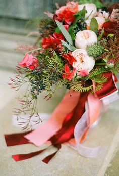 A winter wedding bouquet with blush garden roses, pink protea, greenery, and berries by @hollychapple   Brides.com