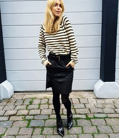 Pernille Teisbaek wears a striped sweater, belted knee length skirt, tights, and patent leather ankle boots