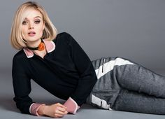 Bella Heathcote lying on the ground in a black top and gray pants