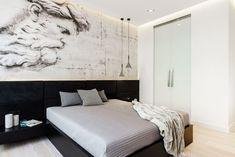 Lakierowana na czarno skrzynia łóżka z wezgłowiem tapicerowanym aksamitem tworzy elegancką bazę wystroju tej sypialni. Jej uzupełnieniem jest ściana wyklejona tapetą, której nadruk przypomina klasyczne malowidło. Zamiast tradycyjnej lampki nocnej przy łóżku zawieszono designerskie betonowe lampy Aplomb marki Foscarini.