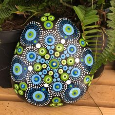 Dot mandala hand painted on a 5 rock. It has been sealed to protect it. I recommend periodically resealing if exposed to the elements.