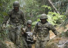 Seabees from Naval Mobile Construction Battalion (NMCB) 3 carry a mock casualty on an improvised stretcher through the jungle while running a six-hour endurance course at the Marine Corps Jungle Warfare Training Center (JWTC).