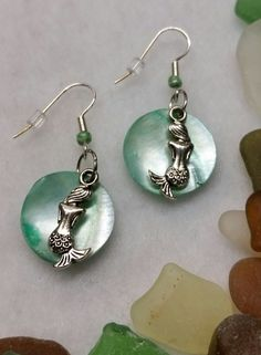 Handmade earrings by BSODesigns. I love the blue shell behind the mermaids!  A cute mermaid charm sits against a dangling shell in these cute, 1 1/2 Earrings with surgical steel fish hooks. A glass bead accents each earring.