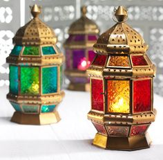 Moroccan style iron lantern with two-tone patterned glass panes and an antique gold coloured finish, made on a fair trade basis. Can be hung or placed on a table inside or outside for a warm glow and an authentic Moroccan atmosphere.
