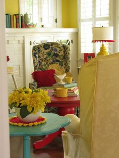Living room @ Daisy Cottage.  LOVE the slip covered wing chair & bright red coffee table!