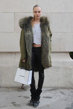 Cara Delevingne StyleChi Army Green Coat Fur Lining Hood Part Leather Black trousers Strappy Biker Boots White Pocket Striped T-Shirt Hair Pulled Back No Make Up Effect Fashion Week Paris, American Apparel, Helmut Lang, Steve Madden, Cara Delevingne Style, Pulled Back Hairstyles, Models Off Duty, Model Pictures, Leggings